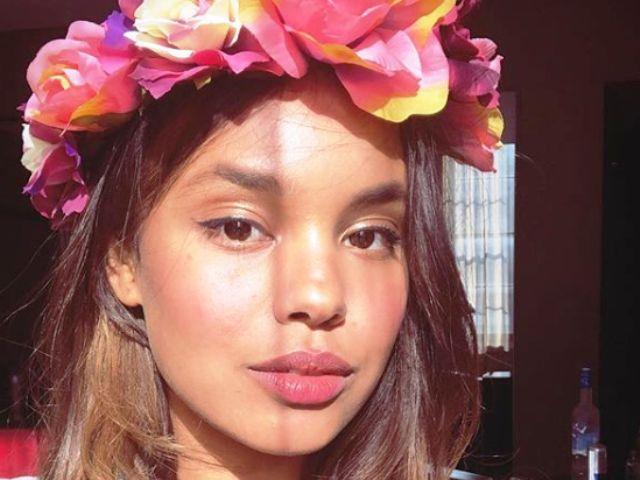 Una foto di primo piano di Alisha Boe con una corona di fiori in testa